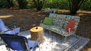 Metal Couch with Flower cushions and two blue chairs