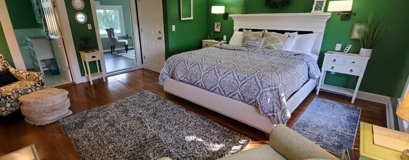 Dark green walls, hardwood floors white headboard