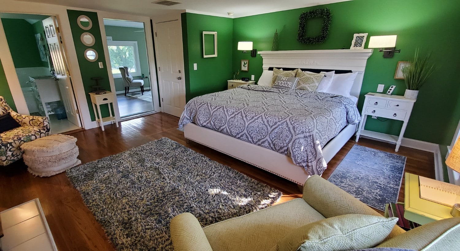 Dark green walls, hardwood floors white headboard