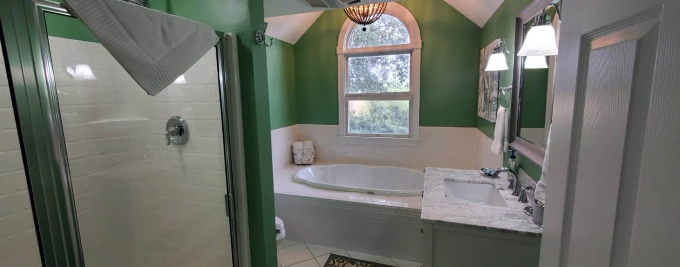 Green bathroom with white counter top and soaking tub