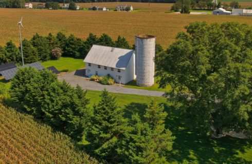 drone shot of the white barn with a white silo