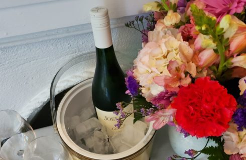 vase with mixed color flowers and a bottle of red wine