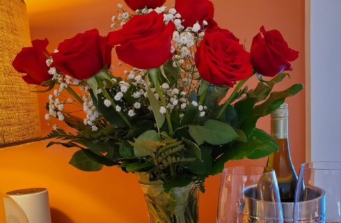 Red roses with a bottle of red wine
