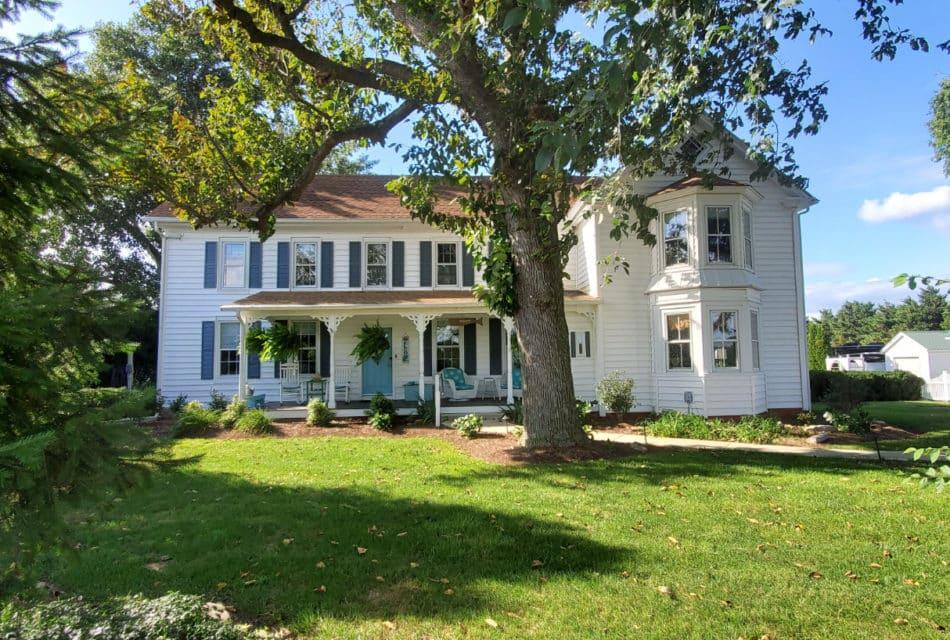 white farm house will green trees