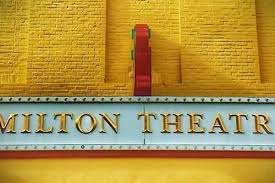 Milton theatre sign yellow and red on brick building