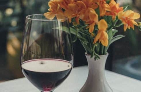 glass of red wine and orange flowers